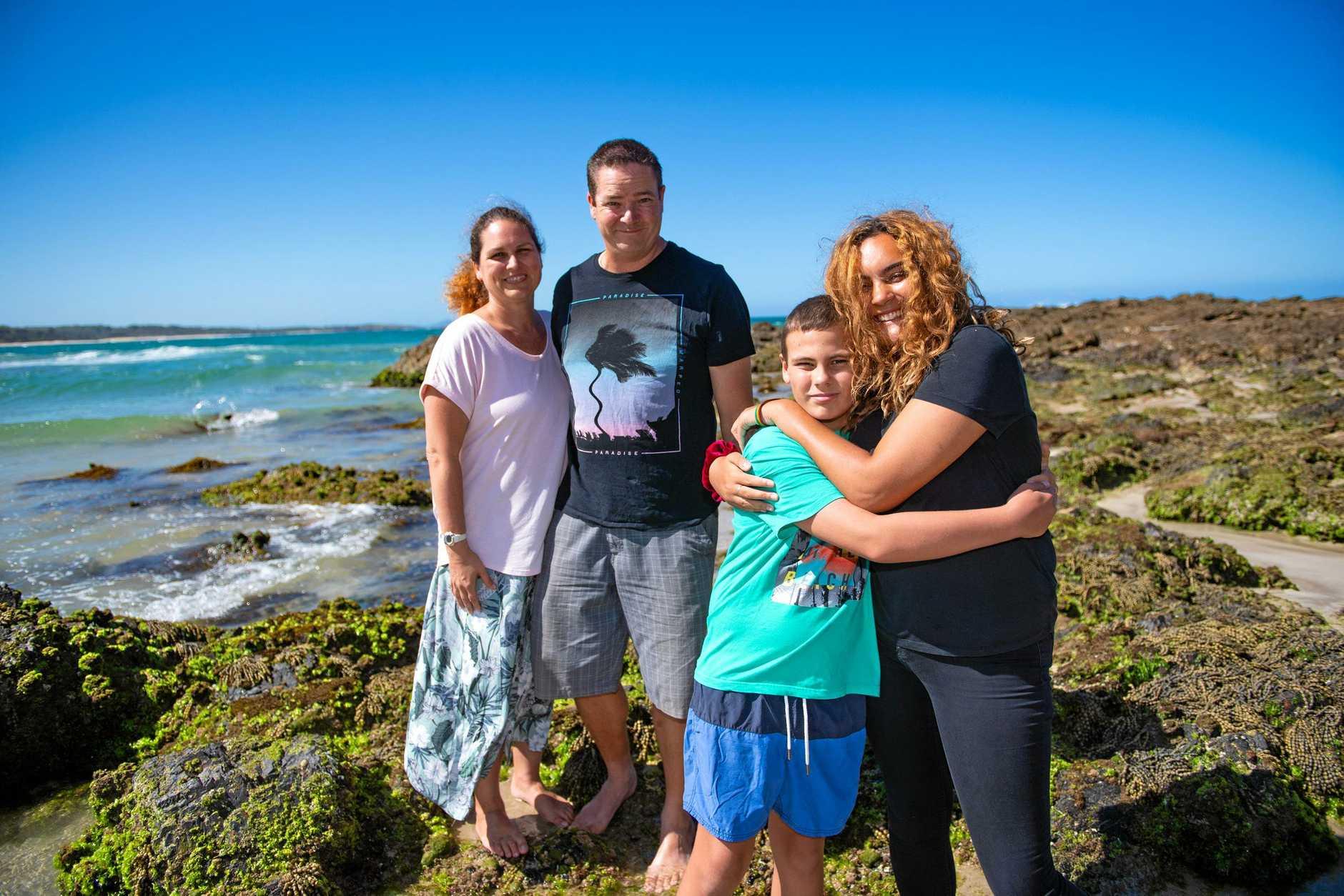 BACK ON DRY LAND: Megan, Aaron and Kaleb Hart with Sofia Pietribiasi at Woolgoolga beach.