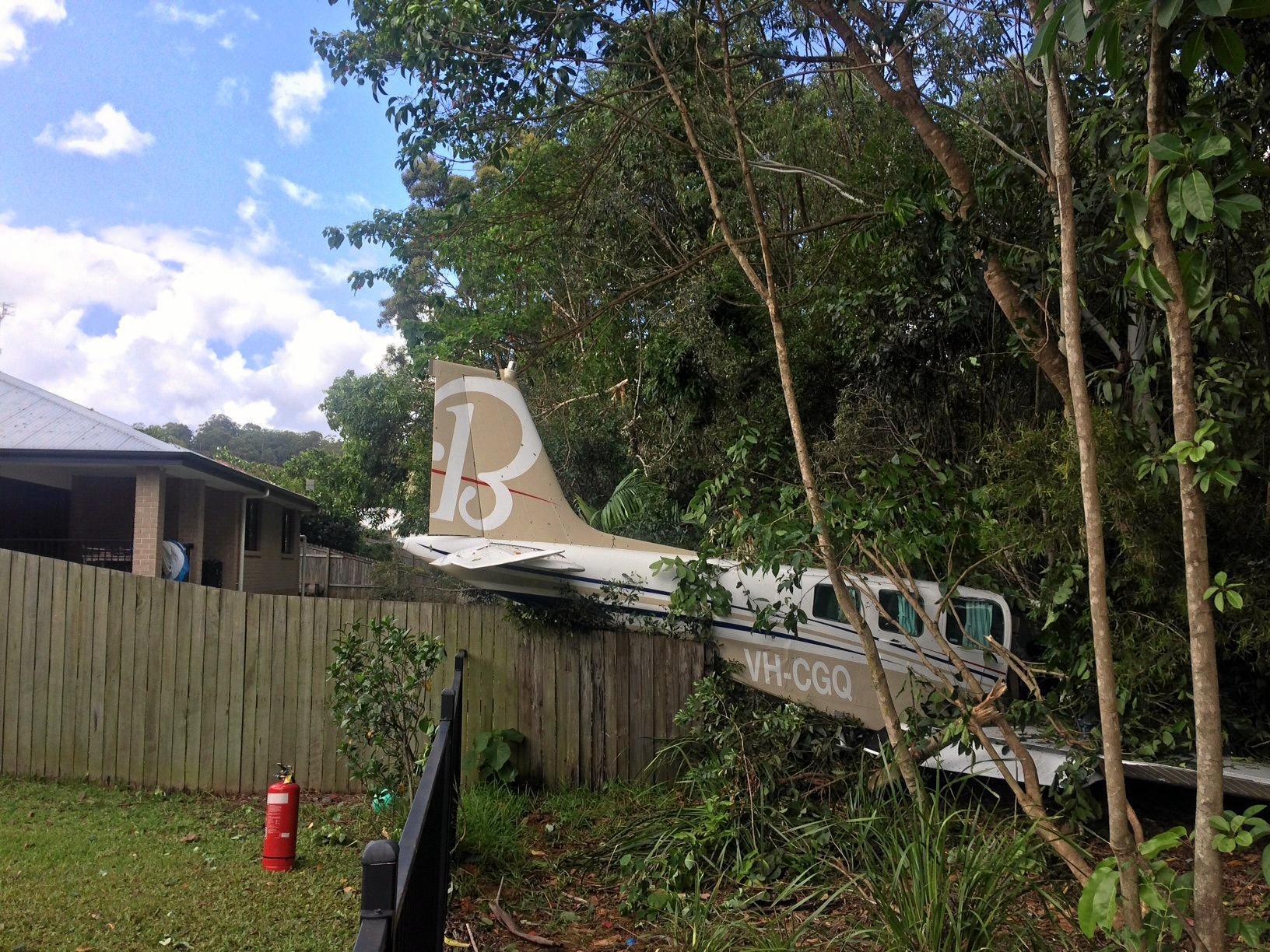 The pilot was forced to make an emergency landing into a private property, crashing through a fence and into trees.