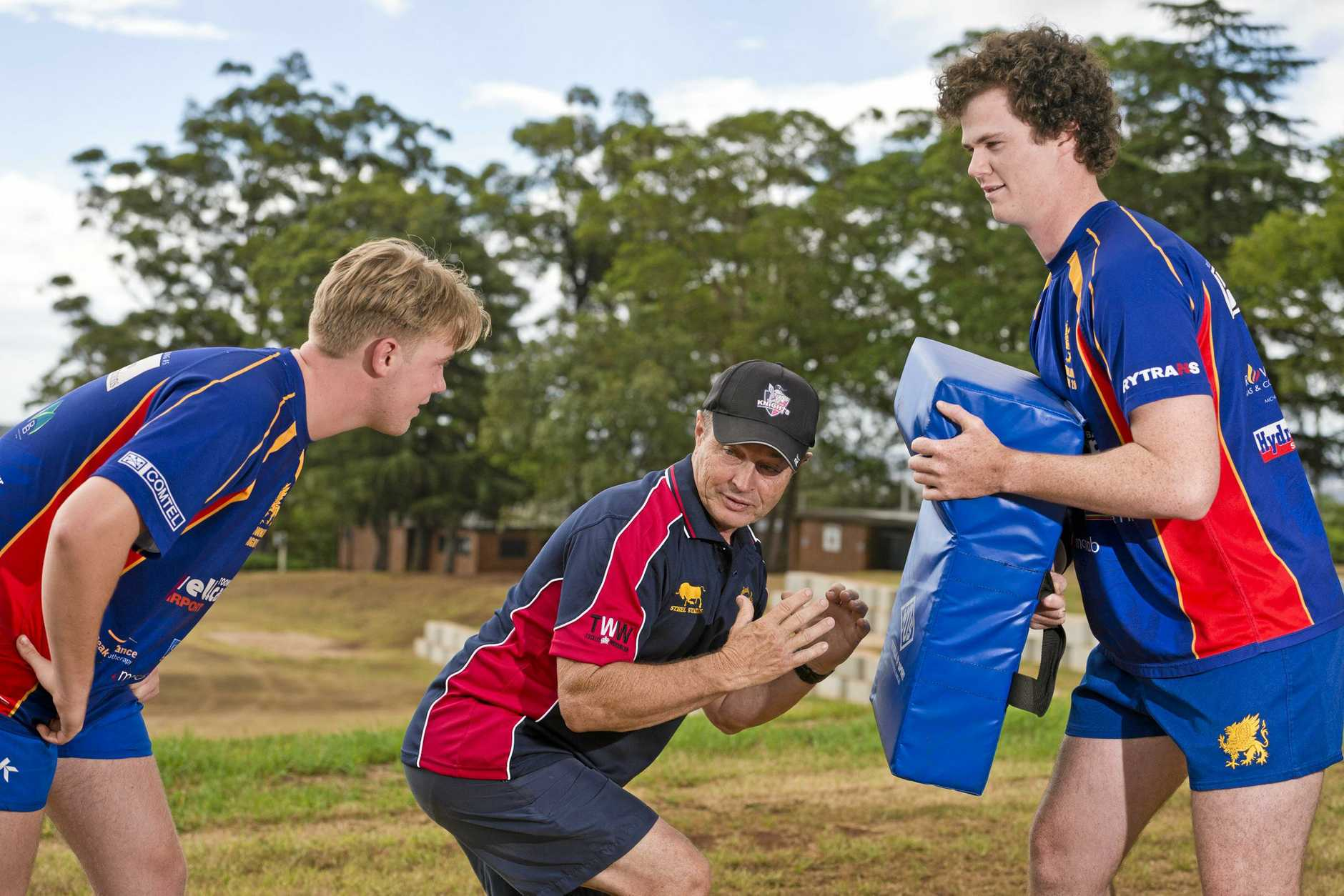 ON BOARD: Downlands rugby players Ned Williams (left) and Mick Ryan run through a tackling drill with defensive coach Graham Herlihy.