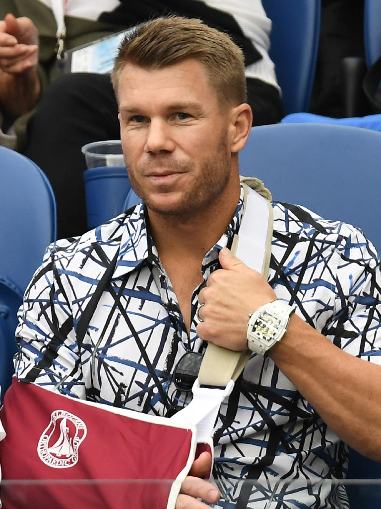 Australian cricketer David Warner is spotted at the Australian Open with his arm in a sling after recent elbow surgery. Picture: AAP