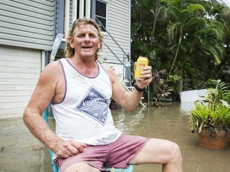 Greg Copnell, who stayed on at his Hermit Park home despite warnings, enjoys a beer in his front yard. Picture: Lachie Millard