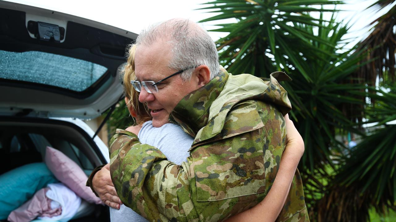 Prime Minister Scott Morrison is seen hugging a resident in a flood affected area in Townsville, Tuesday, February 5, 2019. (AAP Image/Dave Acree)