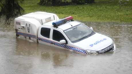 A police car is seen partially submerged in a drain. Picture: Ian Hitchcock/Getty Images