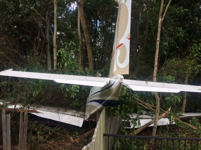 The pilot was forced to make an emergency landing into a private property, crashing through a fence and trees. John McCutcheon.