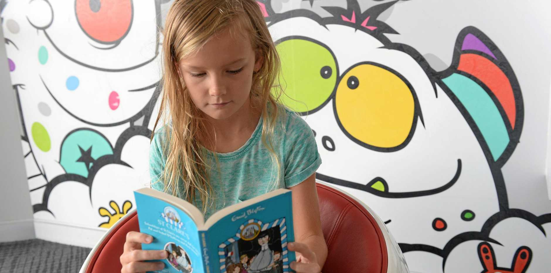 Annabelle Hudson enjoys reading the latest novel, The O'Sullivan Twins at St Clare's, from the Enid Blyton collection at the Dudley Denny City Library.