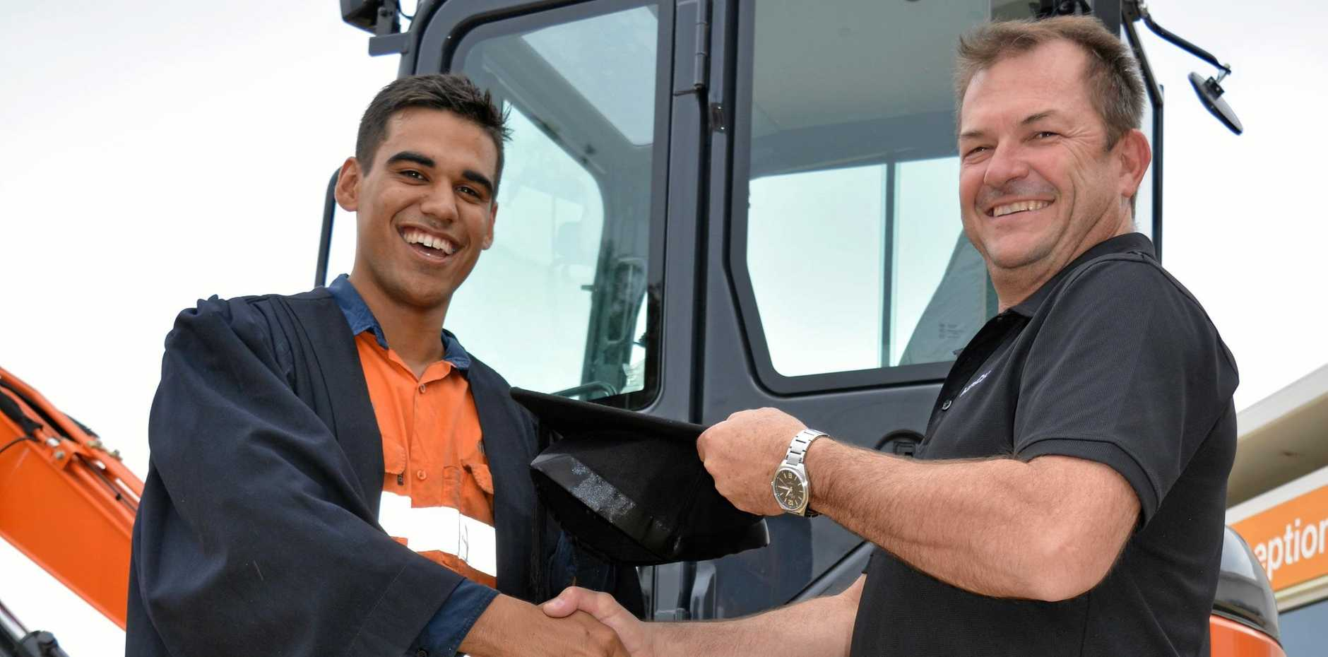 EXCITED: CQUniversity student Jackson Morgan (with Hitachi Workshop supervisor Geoff Wills) will be graduating at the first ceremony in Emerald with a Certificate III in Mobile Plant Technology.
