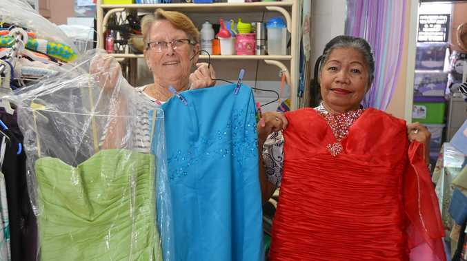 FROCKS: Maria White and Clare McGilvery show the formal gowns you can buy at local op shops.