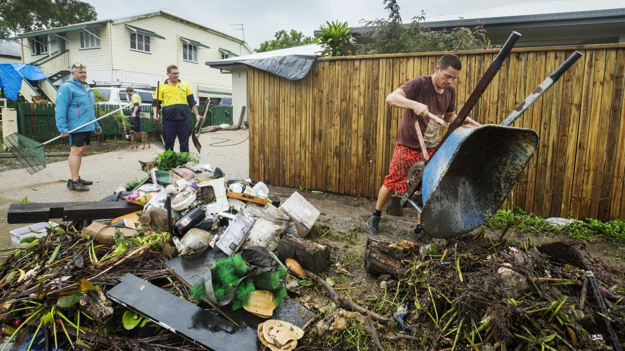 Clinton Smith empties a wheelbarrow of waste from his flood damaged property at Hermit Park. Picture Lachie Millard