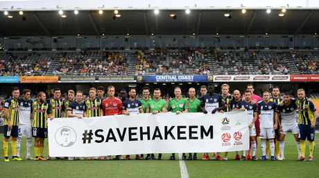 Central Coast Mariners and Melbourne Victory players, along with match officials hold a banner in support of detained footballer Hakeem al-Araibi