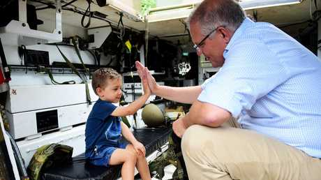 Prime Minister of Australia Scott Morrison visits Idalia in Townsville to survey the aftermath of the floods. Cooper Egan 3 having a tour of an M113 APC .Picture: Alix Sweeney