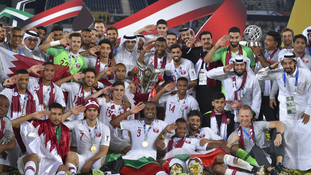 Players and team staffs of Qatar pose for photographs after winning the AFC Asian Cup final