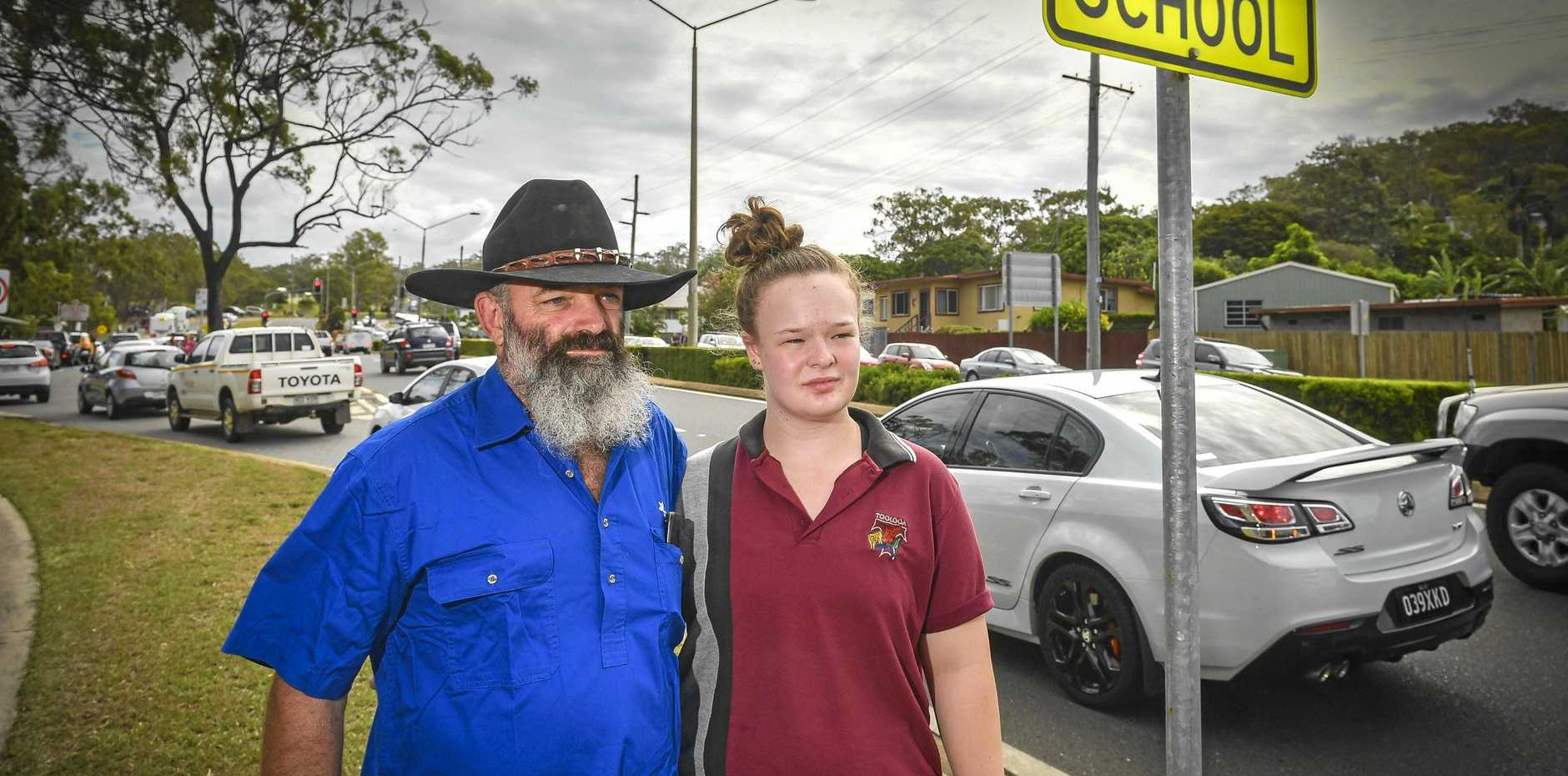 TRAFFIC CHAOS: Isabelle Thompson with stepfather Scott Elwell say the roundabout near the stop, drop and go zone at Toolooa State High is dangerous, after Isabelle had a minor traffic accident on her way home from school.
