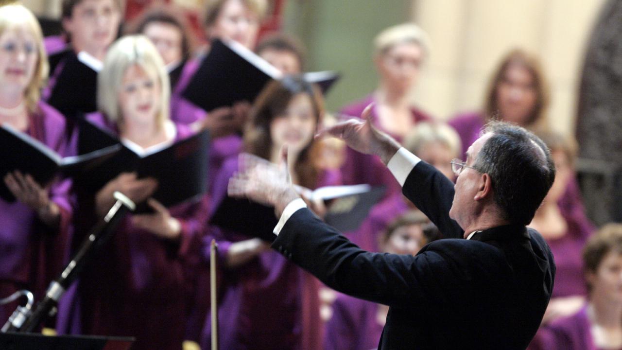 Queensland Choir chorus master Kevin Power leads choristers.