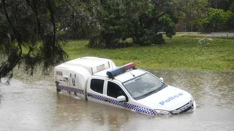 A police car partially submerged in a drain after being swamped by floodwaters in Townsville. Picture: Ian Hitchcock/Getty Images
