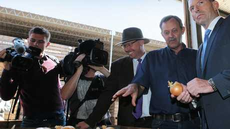 Tony Abbott with Charlton Farm Produce director David Addison seconds before he made the onion in his hand Australia's most famous vegetable.