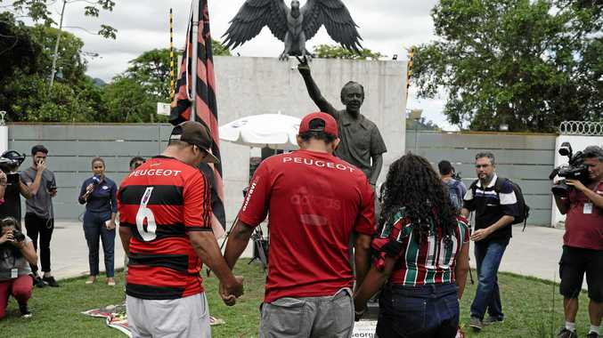 Fans hold hands as they pray in a homage to the victims of a fire at the Flamengo soccer club training complex in Rio de Janeiro, Brazil. Picture: Leo Correa/AP