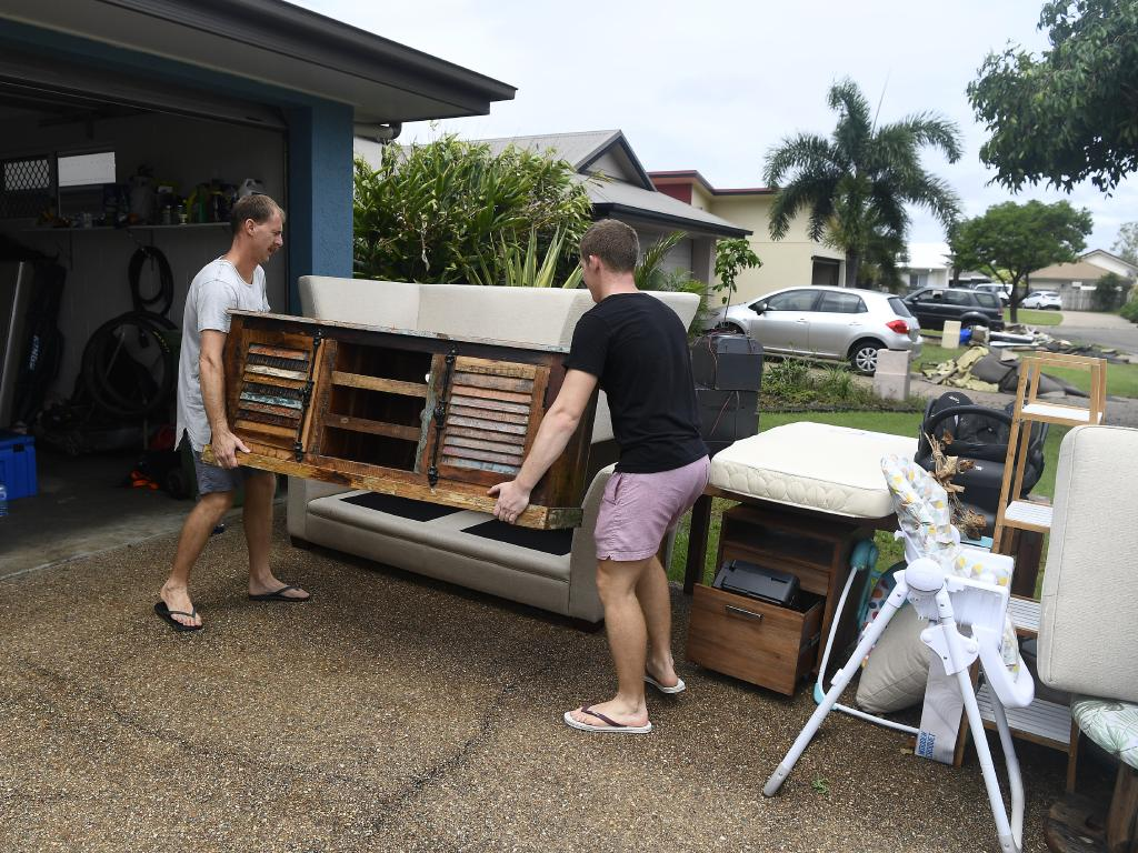 Townsville residents Nathan Graham and Sean Graham dump flood damaged furniture outside their home in the suburb of Idalia in Townsville, Australia. Picture: Getty
