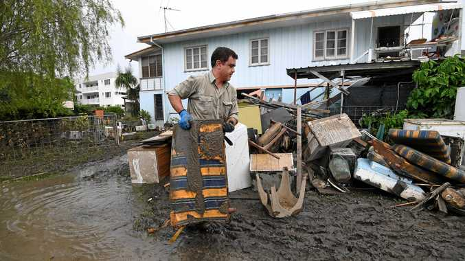 A man helps total strangers to remove flood-damaged items from their home in the suburb of Rosslea in Townsville, Thursday, February 7, 2019. Residents have begun cleaning up after days of torrential rain and unprecedented water releases from the city's swollen dam, sending torrents of water down the Ross River and into the city, swamping roads, yards and homes. (AAP Image/Dan Peled) NO ARCHIVING