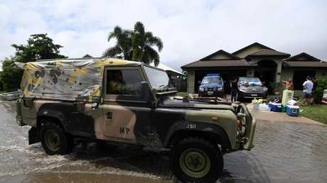 An army vehicle drives past houses affected by floods in the suburb of Hermit Park. Picture: AAP Image/Dan Peled