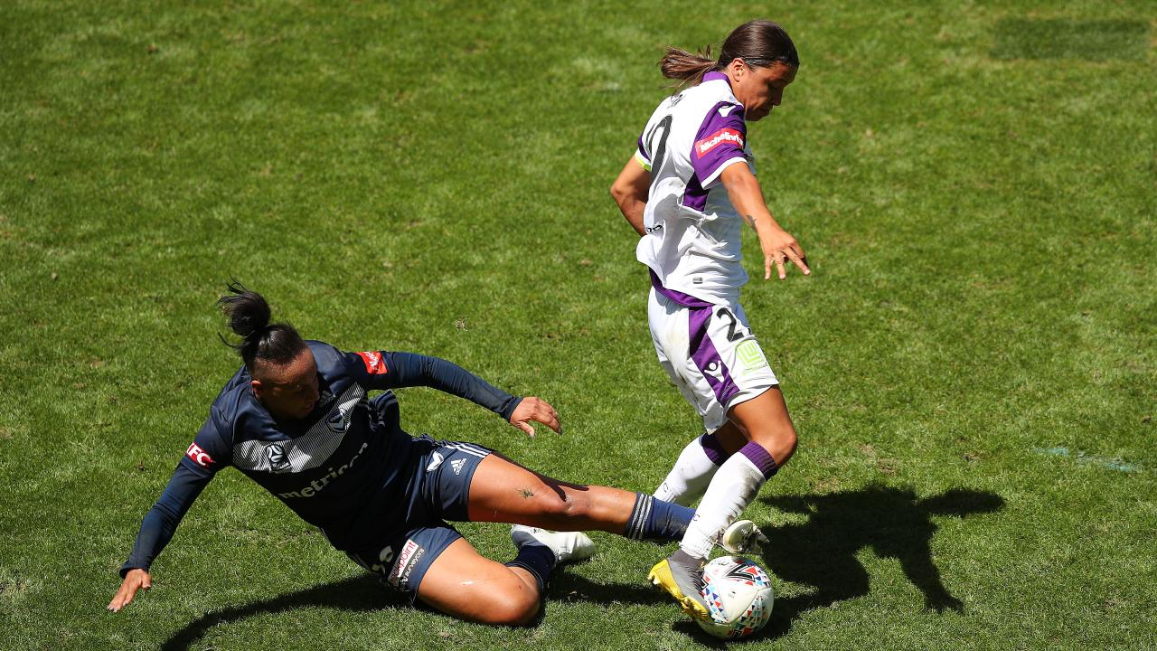 Victory's Samantha Johnson slide in to tackle Sam Kerr. Picture: AAP