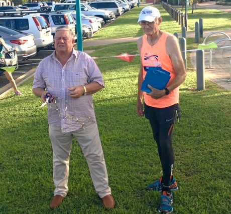Mackay Road Runners club patron Col Meng (left) ready to cut the ribbon to open the 2019 Mackay Road Runners formal season with oldest member, Stuart Sprott, who turns 75 this week.