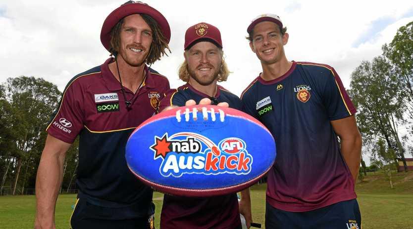 RARING TO GO: Gympie's Brisbane Lion Tom Fullarton (far right) with teammates Matt Eagles and Daniel Rich at Jones Hill State School yesterday morning.