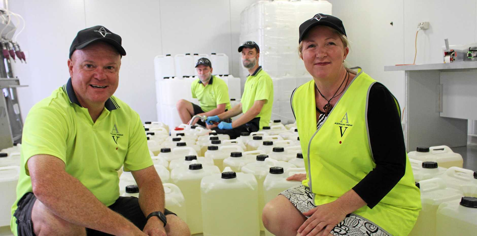 HELPING OUT: Ian Henderson and Josie Howard and (back) vinegar makers Michael Britten and Joerg Achenbach with just some of the bottles sent to Townsville.