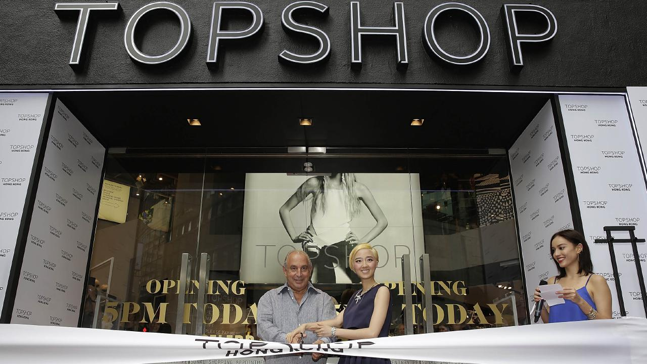 Topshop owner Sir Philip Green and Taiwanese actress Gwei Lun Mei cut a ribbon to mark the 2013 opening of a new Topshop store in Hong Kong as TV host Mandy Lieu watches on. Picture: Jessica Hromas/Getty Images