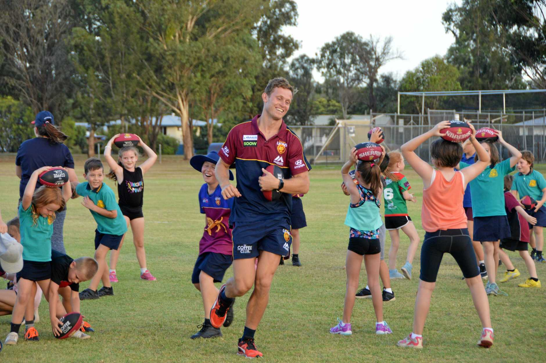 Brisbane Lions players Ryan Lester having fun playing stuck in the mud in Kingaroy.