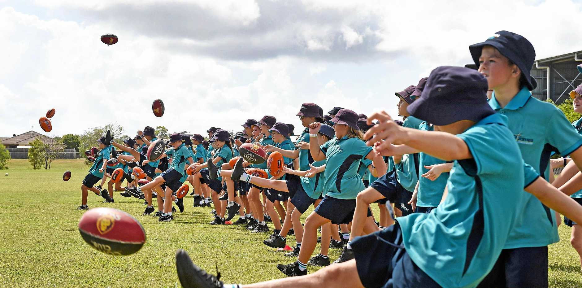 FUTURE ATHLETES: Students launch the footies during the Brisbane Lions' visit to St James Lutheran College yesterday.