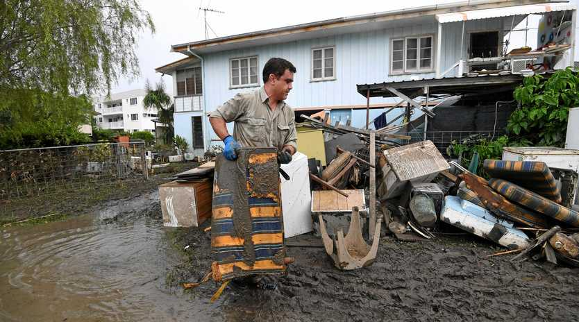 A man helps total strangers to remove flood-damaged items from their home in the suburb of Rosslea in Townsville, Thursday, February 7, 2019. Residents have begun cleaning up after days of torrential rain and unprecedented water releases from the city's swollen dam, sending torrents of water down the Ross River and into the city, swamping roads, yards and homes.