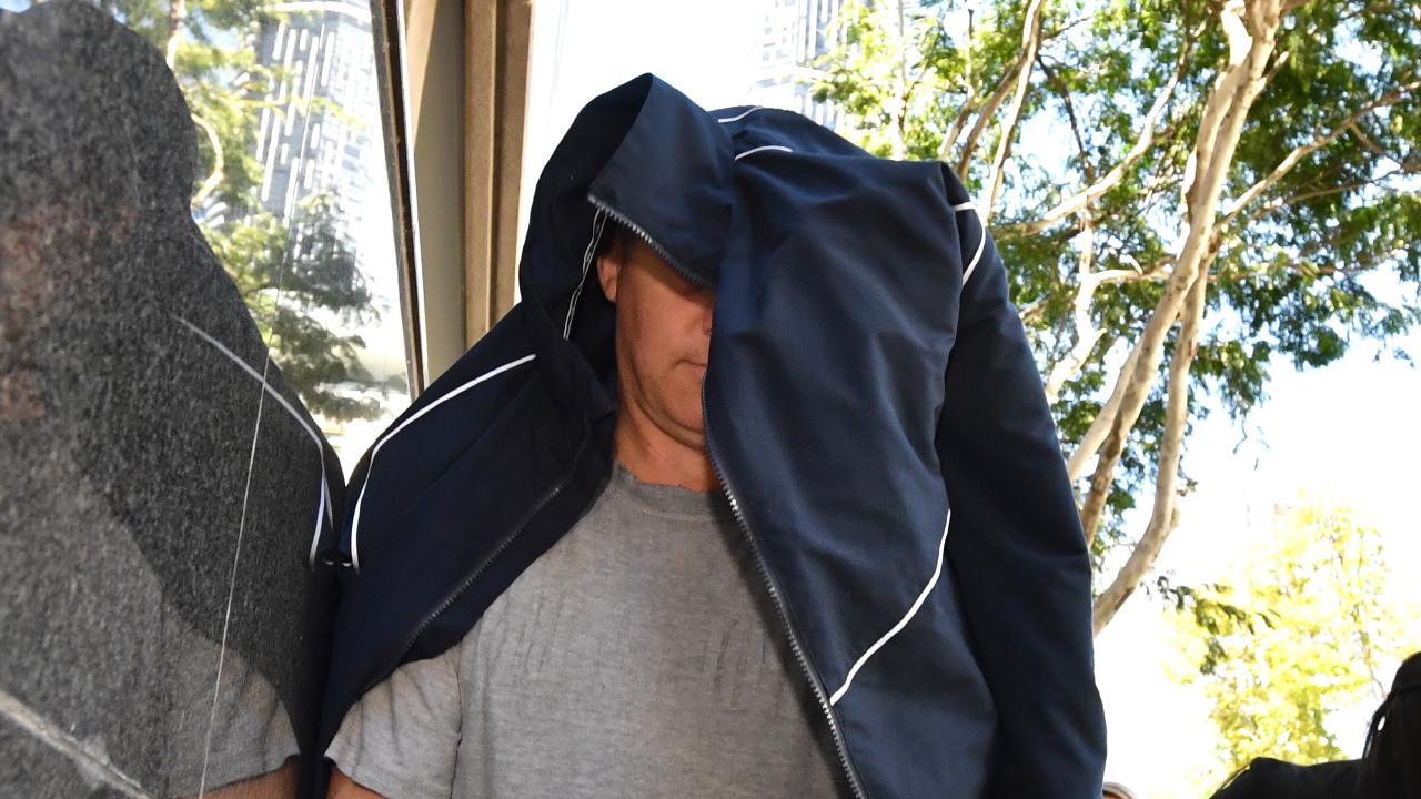 Australian Federal Police officer Gregory Paul Edwards hides from the media after leaving the Brisbane watcchouse in 2017. File picture