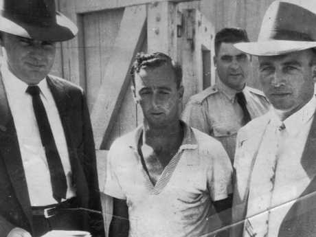 Glen Patrick Hallahan, left, and a Mount Isa officer escort Raymond Bailey, centre, after his arrest. File picture