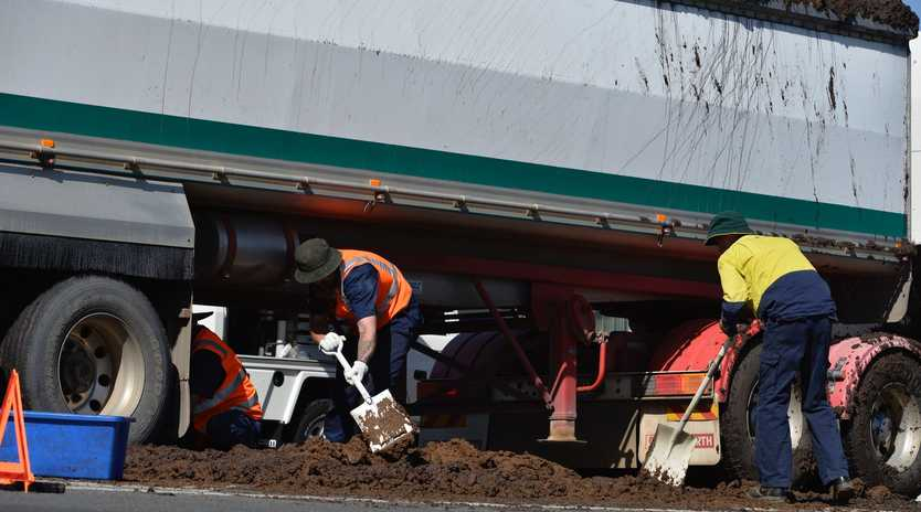 Council workers clean up after a manure truck loses its load in Torrington.