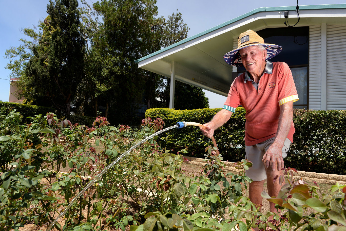 Cec Gleeson hoses his rose bushes at his Eastern Heights property.