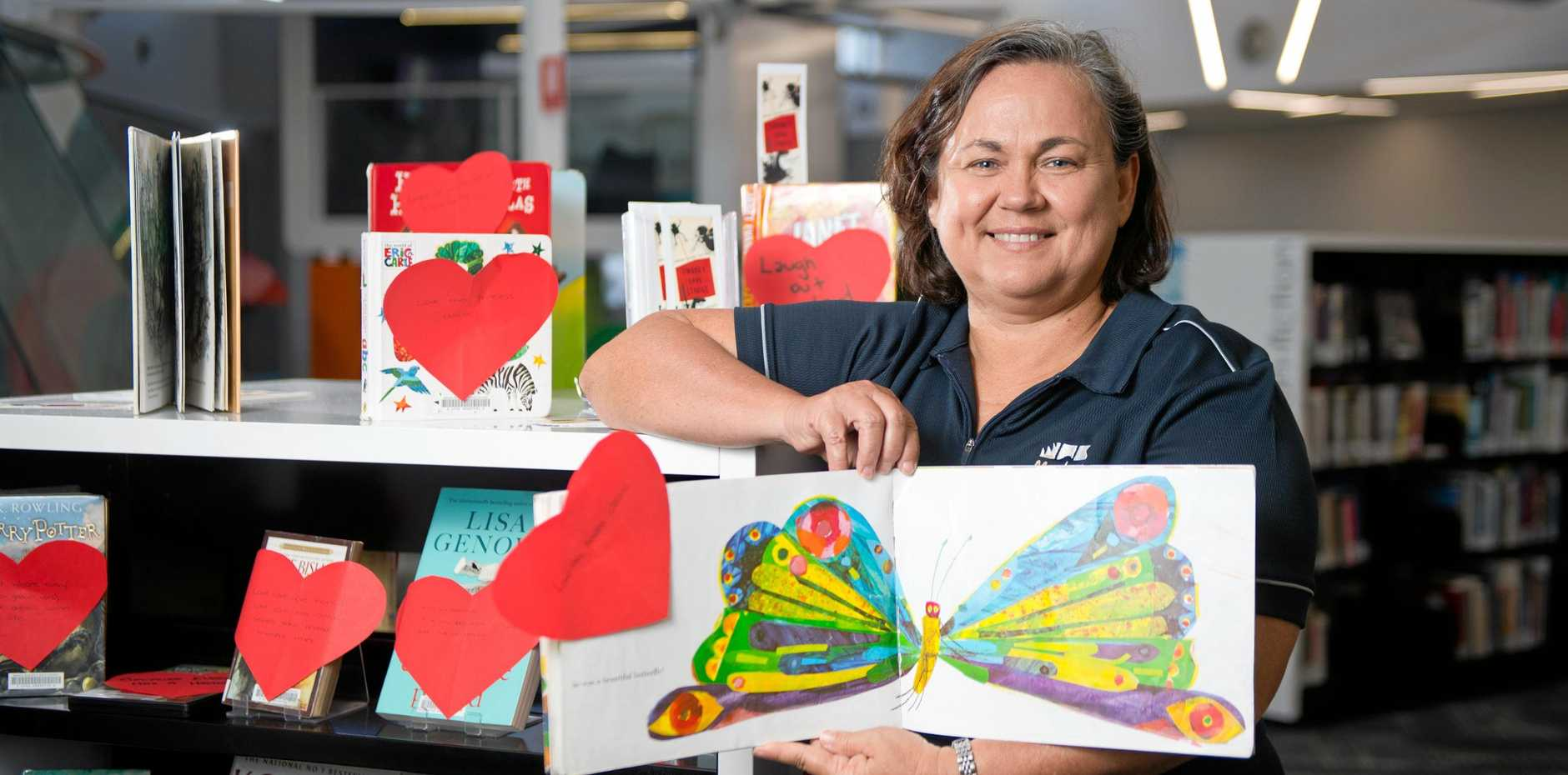 LIBRARY LOVERS: Library Assistant Del Icardi with a collection of books most loved by staff from Mackay Regional Council Libraries. The selection has been put together in honour of Library Lovers' Day, which falls today.