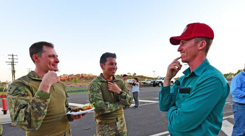 Lieutenant Dan Moore and Lieutenant Andrew Kahara from 5th Aviation Regiment talk with grazier Luke Chaplin as the Army arrived in Cloncurry to drop off supplies to farmers affected by the floods. Picture: Zak Simmonds