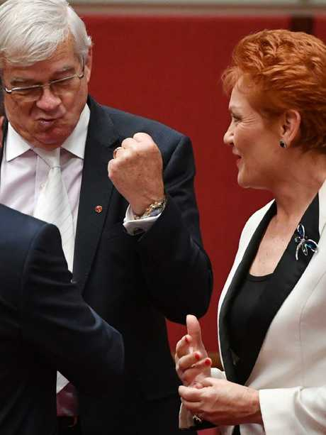 One Nation leader Senator Pauline Hanson looks on as One Nation Senator Brian Burston gives One Nation Senator Peter Georgiou a fist pump after his maiden speech in Canberra, Wednesday, August 16, 2017. Picture: AAP/Mick Tsikas