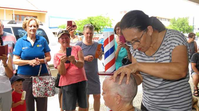 LOCKS LOPPED: Supporters, friends and onlookers snap photos as Sharon Coell has her hair shaved off on Poinciana Avenue, Tewantin.