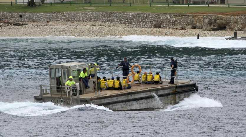 A group of Vietnamese asylum seekers are taken by barge to a jetty on Australia's Christmas Island. Picture: AP