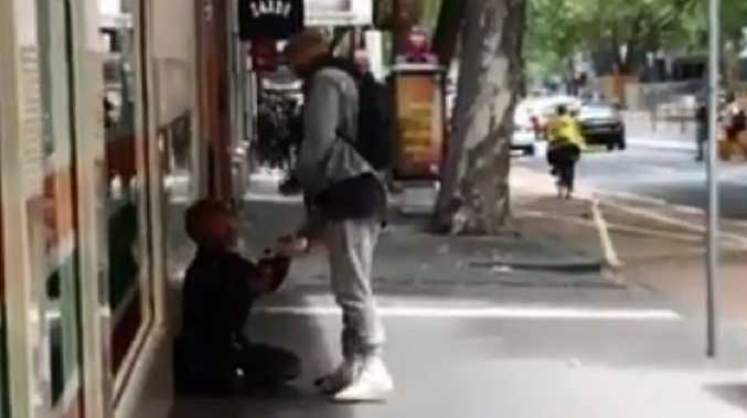 Quade Cooper gives food and drink to a homeless man in Melbourne.