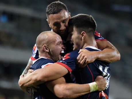 Rebels Billy Meakes and Quade Cooper congratulate Jack Maddocks after his try. Picture: Mick Tsikas/AAP