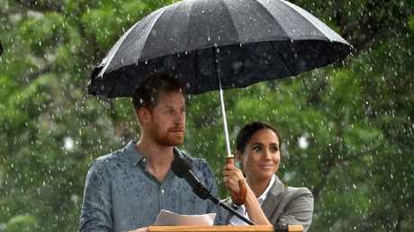 Harry speaks to the Dubbo community as Meghan holds an umbrella. Picture: Peter Parks/AAP