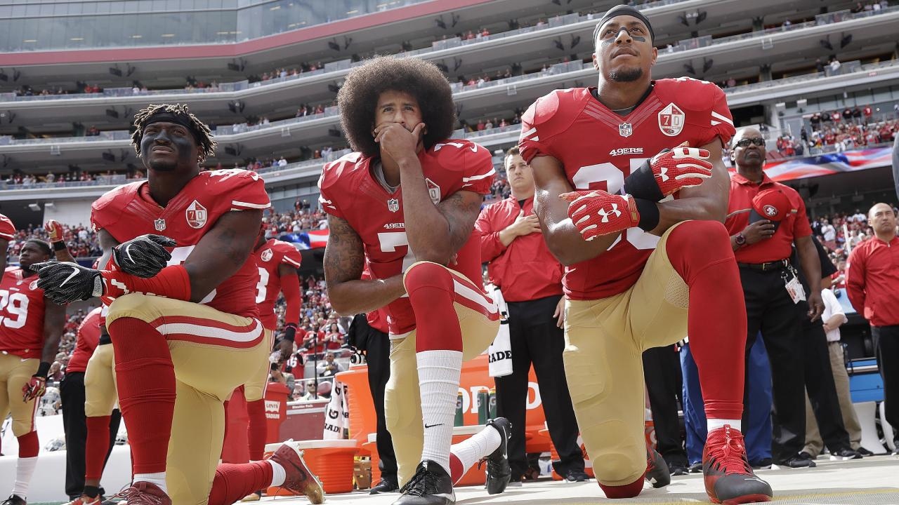 Colin Kaepernick, centre,  and the NFL have settled their collusion case. Picture: AP