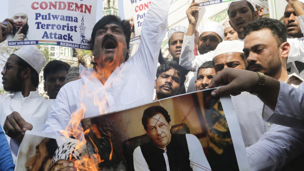 Indian Muslims burn posters of Pakistani prime minister Imran Khan, centre, and Hafiz Saeed, chief of Pakistani religious group Jamaat-ud-Dawa. Picture: Rajanish Kakade/AP