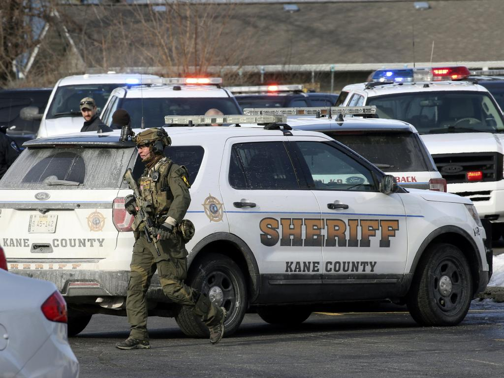 Law enforcement personnel gather near the scene where an active shooter was reported in Aurora. Picture: Antonio Perez/Chicago Tribune via AP