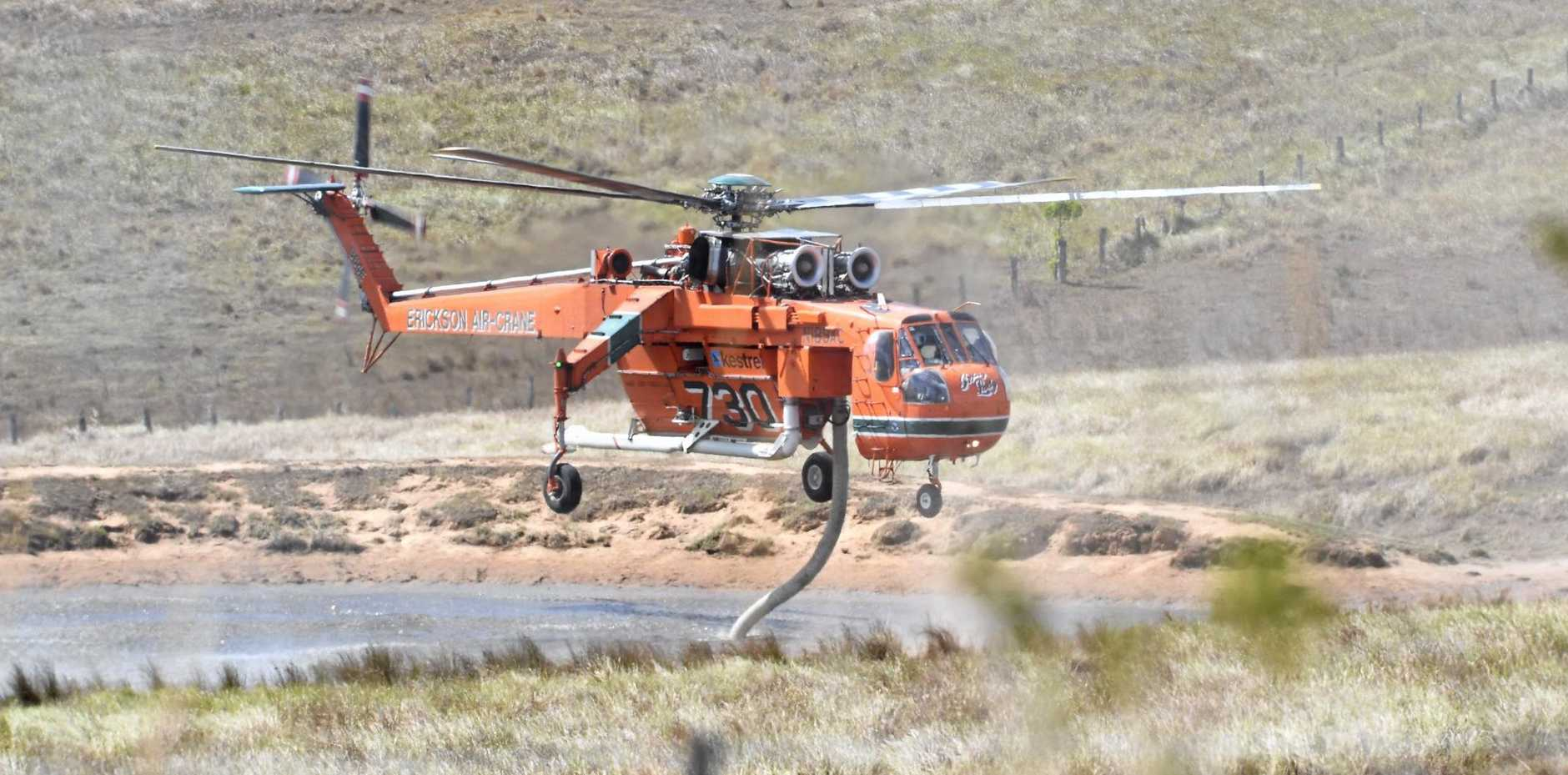 FIGHTING FIRES: The Elvis helicopter, which can hold 9,500 litres (2,500 US gal) of water, fills up for another drop. INSET TOP: Paula Avery with Rocky Laurie, 3 months, after being dropped off by buses back to Jumbullum Village following the fires. INSET BOTTOM: Fire trucks patrol the parched earth around Tabulam.