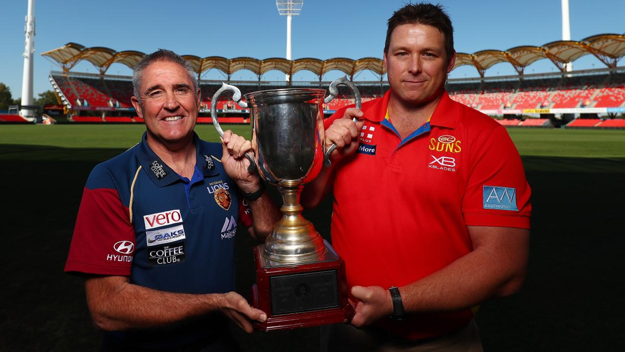 Brisbane coach Chris Fagan and Suns counterpart Stuart Dew with the QClash Cup.