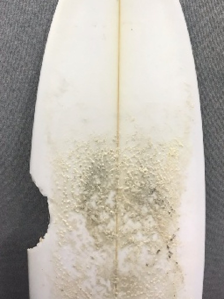 The bite marks on the back of the surfboard.