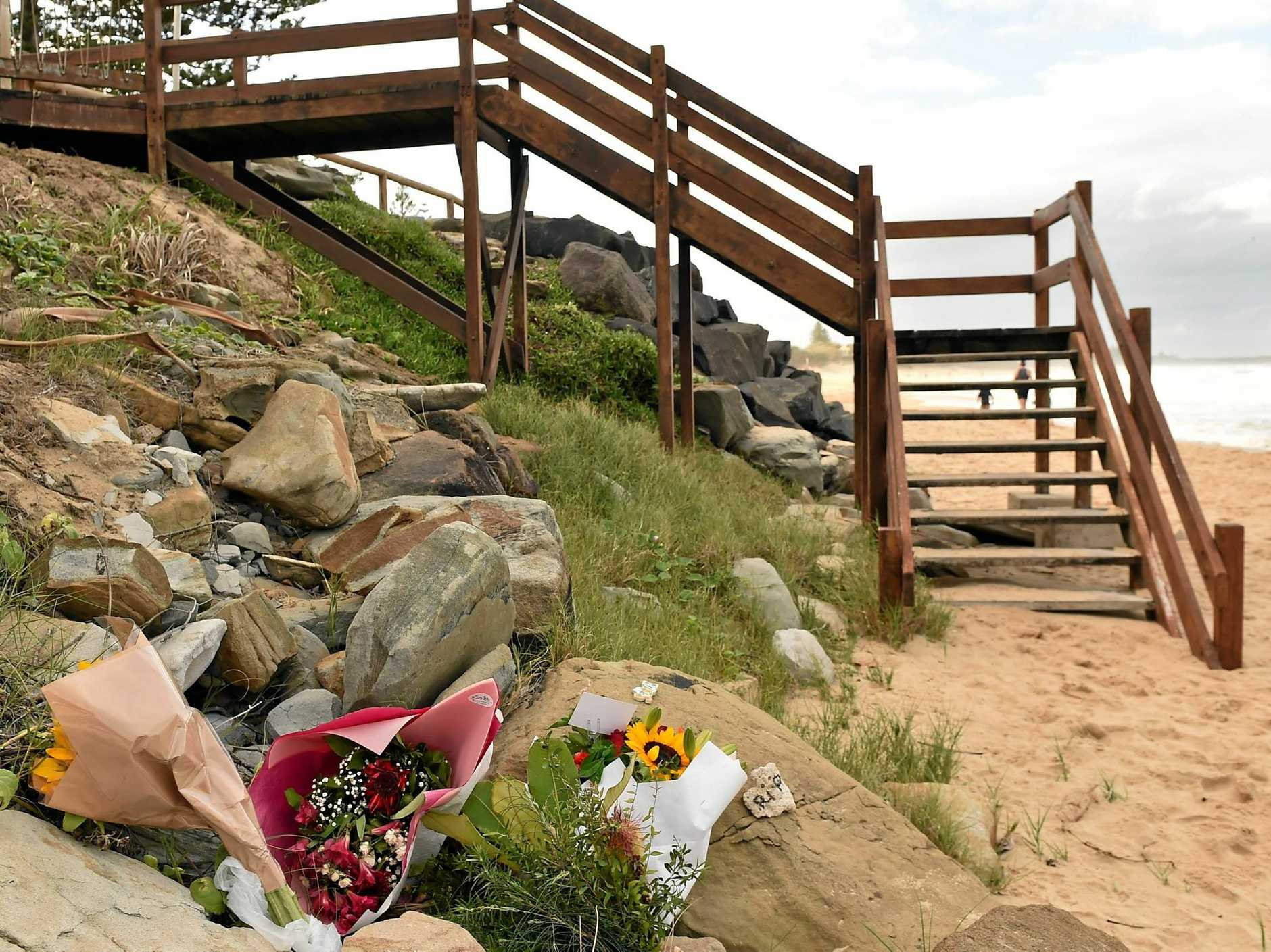 The Dicky Beach surfing community is reeling after the body of a young woman washed ashore. Flowers have been left at the bottom of the staircase in her remembrance.